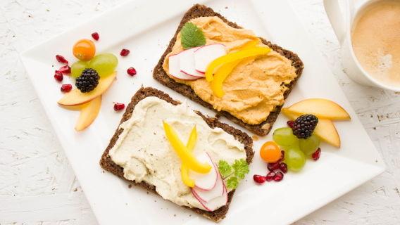Weißer Frühstücksteller mit Schwarzbrot, Gemüse, Obst und dazu ein weißer Becher mit Kaffee. Pixabay.com Foto (1804457): Bernadette Wurzinger