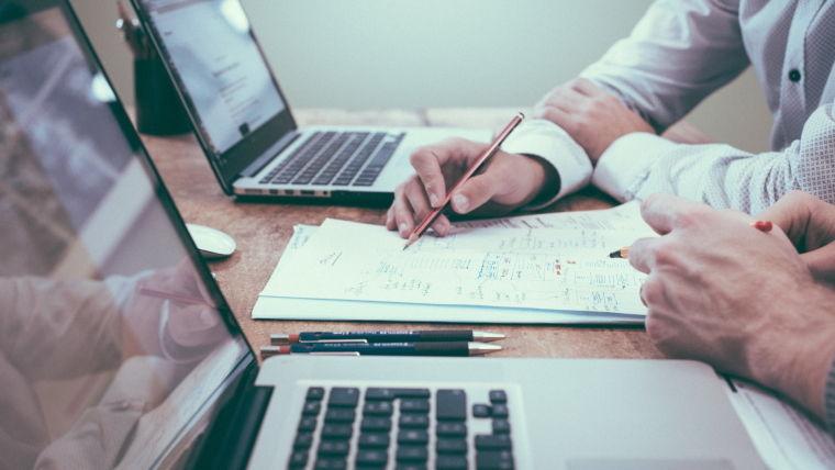 Zwei Bürokollegen sitzen zusammen vor zwei grauen Notebooks und tauschen sich über ihre Arbeitsergebnisse aus. Pixabay.com Foto (1209640): Free-Photos