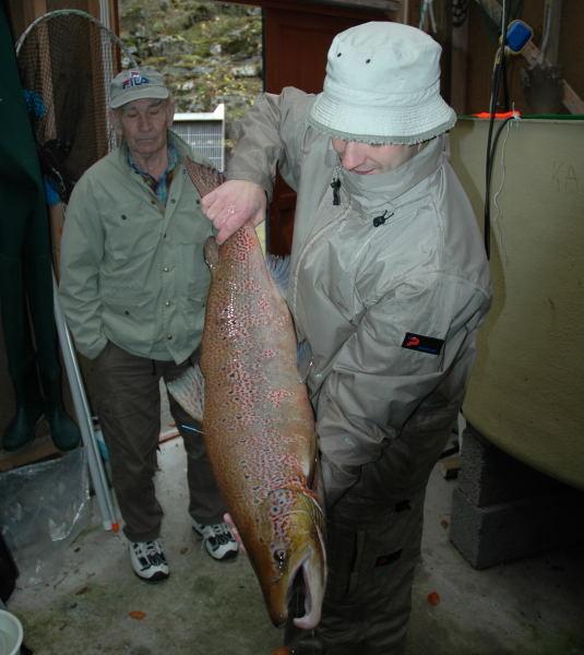 Odd Rune Hvidsten med ein hannlaks på 8.9kg. I bakgrunnen står Georg Bakke og betraktar fisken. Foto: Arne R Sandven