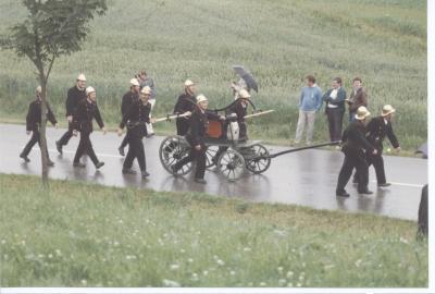 Handbetriebene Wasserspritze vor 1900 - tapfere Männer auf dem Weg zur Brandstelle