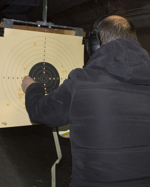 Schütze klebt Zielscheibe ab.