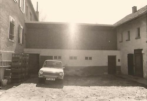 Schwarz-Weiß Foto von einem Hof mit Auto