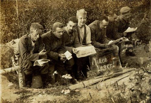 Männer auf einer Stange sitzend, mit Schild Mienen Leger!