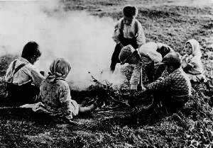 Schwarz-Weiß Foto von Menschen um ein Kartoffelfeuer