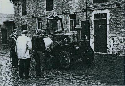 Mehrere Leute betrachten einen alten Traktor
