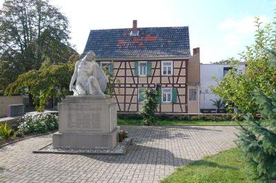 Denkmal mit historischem Haus im Hintergrund