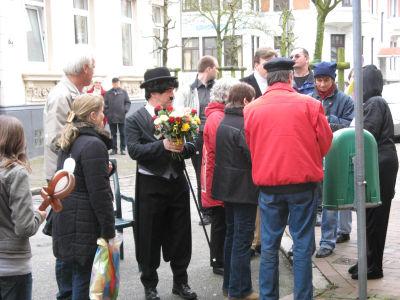 Charly Chaplin verschenkt Rosen an die anwesenden Damen.