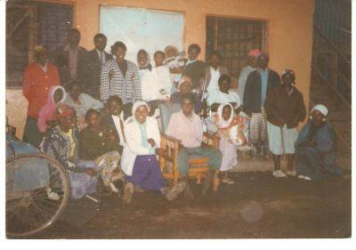Abbildung 1: Bewohner eines Gemeinschaftshauses. Bei genauem Hinsehen stellen Sie Fehlhaltungen und fehlende Gliedmaßen fest. Gelähmte Personen werden sogar unter den Achseln aufrecht gehalten, weil kein Stuhl da ist.