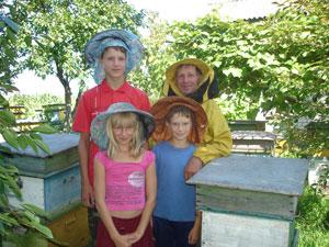 Володимир Іванович Лобур з онуками Олександром, Мариною та Валентином біля вуликів у саду.