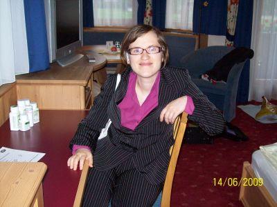 Monika sitzt im Anzug auf einem Stuhl