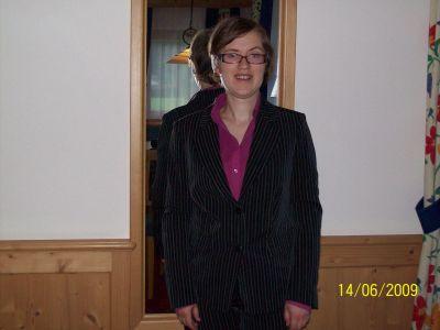 Monika steht in Schale gekleidet vor dem Spiegel