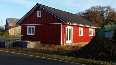 Holzrahmenbau Neubau in schwedenrot gestrichen mit schwarzen Dachpfannen